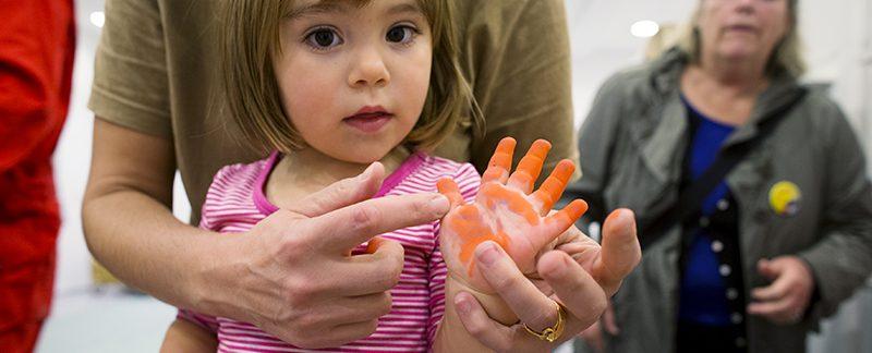 Barn med färg på handen. Foto Maria Sattrup